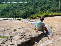 donna legge piedi nell acqua delle cascate termale di bagno vignoni
